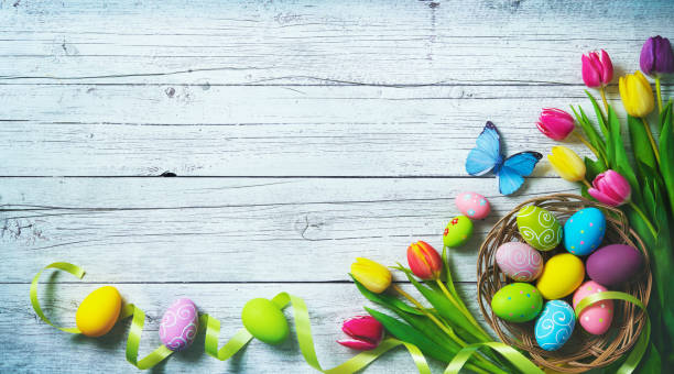 easter background. colorful spring tulips with butterflies and painted eggs - easter foto e immagini stock
