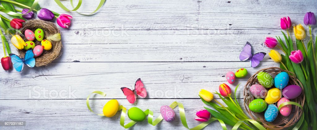 Easter background. Colorful spring tulips with butterflies and painted eggs stock photo
