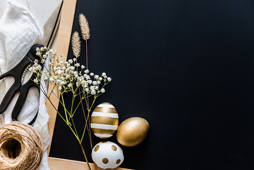 Easter background. Easter eggs in various golden designs, scissors, flowers and hemp ball over black story board. Copy space.