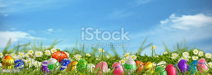 istock Easter background - meadow with Easter eggs and blue sky 933917310