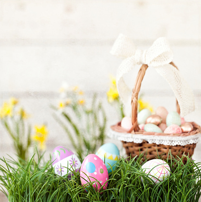 Easter Basket with Easter Eggs in Grass against an Old White Wood Background