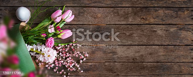 Bouquet of pink spring flowers with easter egg on old rustic boards. Flat lay floral decoration for an Easter background. Horizontal top view with space for text and design.