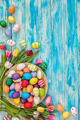 Easter background with painted eggs and colorful tulips, top-down composition