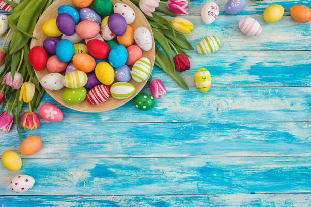 Easter Background with Colorful Eggs and Tulips Easter background with painted eggs and colorful tulips, top-down composition April stock pictures, royalty-free photos & images