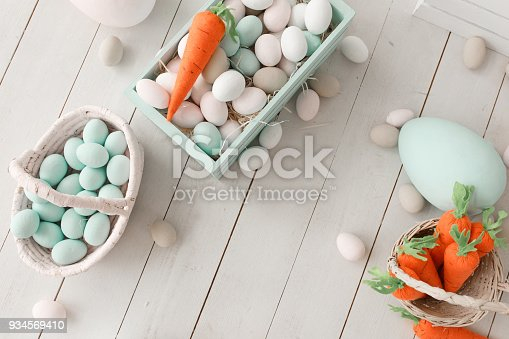 istock Easter background with colorful eggs and yellow orange carrots over white wood. Top view with copy space 934569410