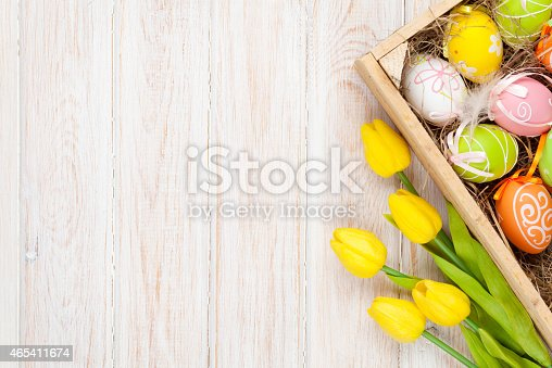 istock Easter background with colorful eggs and yellow tulips 465411674