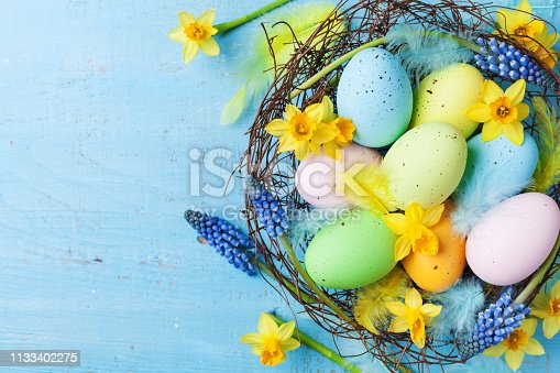 istock Easter background with colorful eggs in nest, feather and spring flowers top view. Holiday card or banner. 1133402275