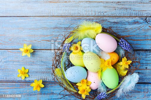 istock Easter background with colorful eggs in nest, feather and spring flowers top view. Holiday card or banner. 1133402309