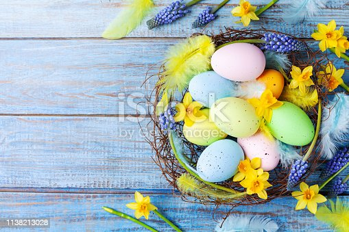 istock Easter background with colorful eggs in nest, feather and spring flowers top view. Holiday card or banner. 1138213028