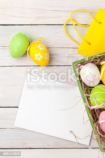istock Easter background with colorful eggs, yellow tulips and greeting 465424826
