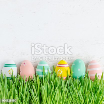istock Easter background with Easter eggs and fresh green grass. Top view with copy space. 930928480
