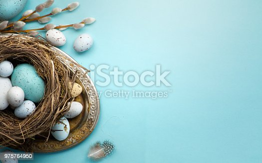 istock Easter background with Easter eggs and spring flowers on blue table 975764950