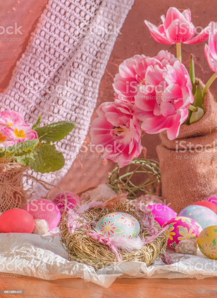 Easter background with eggs in nest and pink tulips. royalty-free stock photo