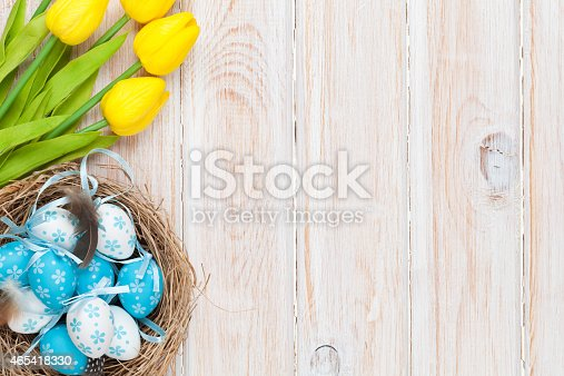 istock Easter background with eggs in nest and yellow tulips 465418330
