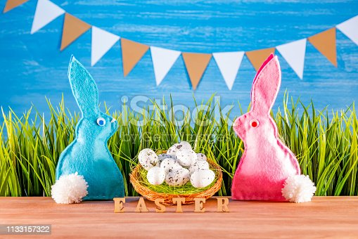 930928526 istock photo Easter background with eggs, rabbits and green grass 1133157322