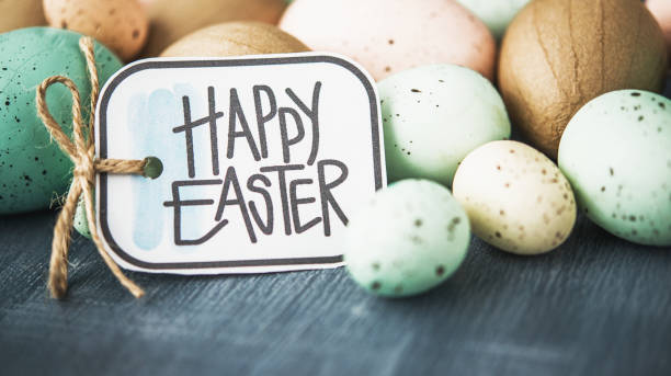 Easter background with pastel speckled eggs on gray and Easter message stock photo