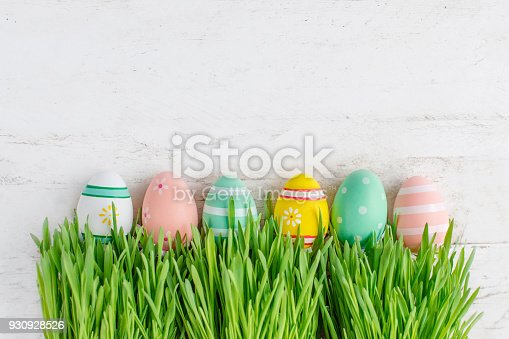 istock Easter background with row of colorful eggs hiding in  green grass, copy space. Top view.  Easter holiday concept 930928526