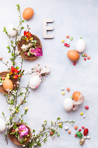 Easter background with various eggs, bunny ears napkin, spring blossom branch,  candies and Easter letter E on the textured surface, top view, copy space