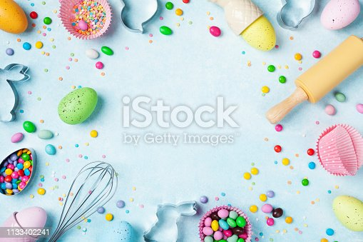 Easter baking background with rolling pin, whisk, decorative eggs, cookie cutters, candy and colorful confetti on kitchen table top view. Flat lay style.