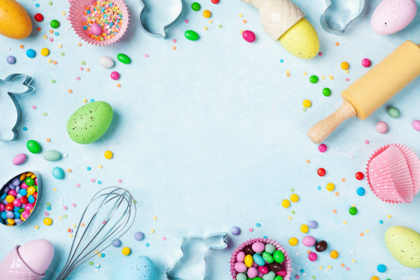 osterbackhintergrund mit nudelholz, schneebesen, dekorativen eiern, keksschneider, süßigkeiten und bunten konfetti auf küchentisch-oberansicht. wohnung gelegt. - backrahmen stock-fotos und bilder