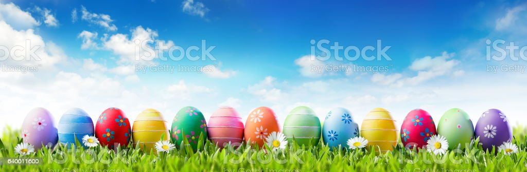 Easter Banner - Colorful Painted Eggs In Row On Grass stock photo