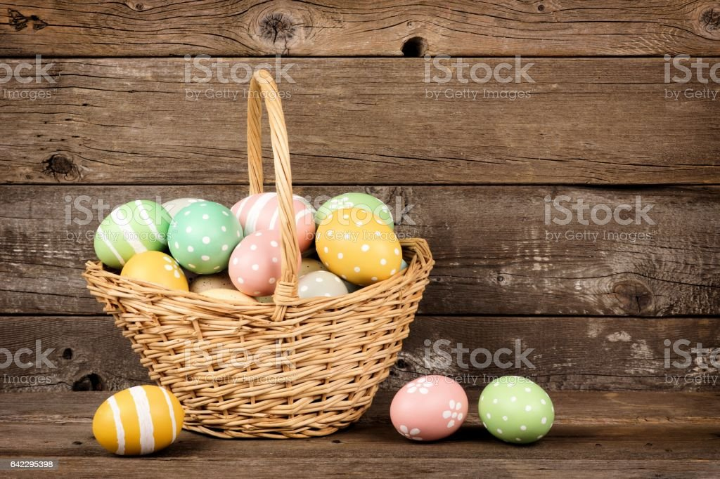 Easter basket filled eggs over rustic wood stock photo