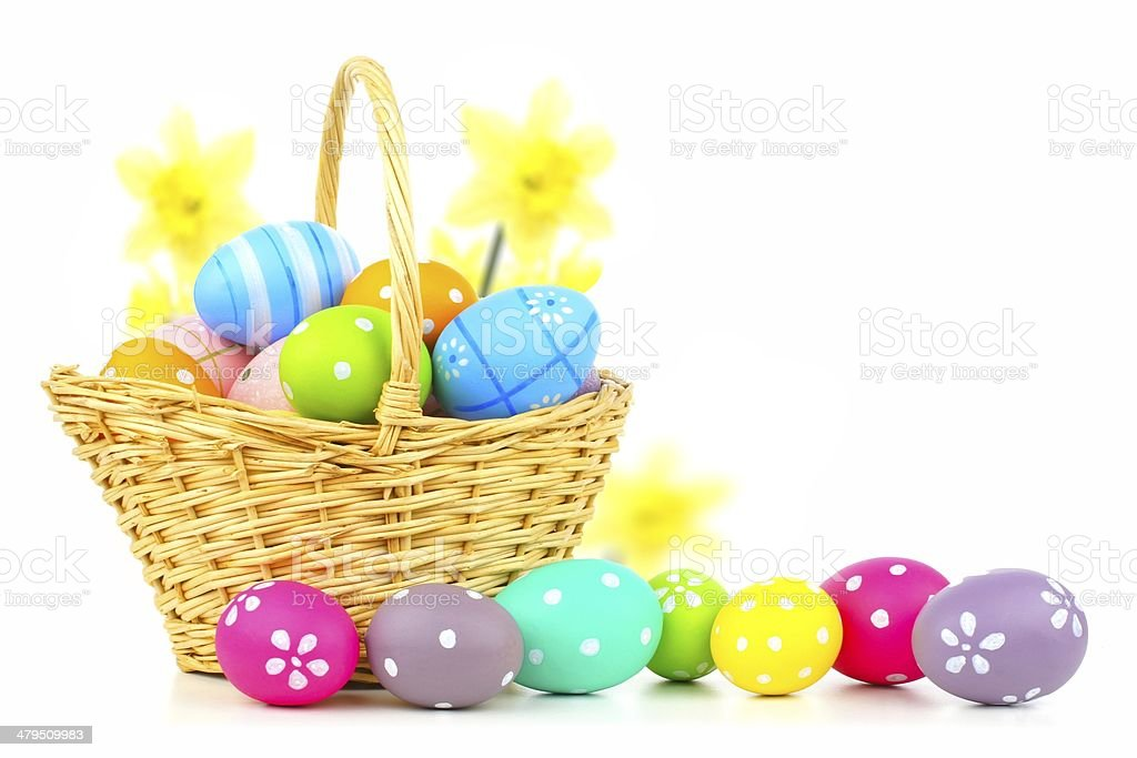 Easter basket filled with eggs and flowers over white stock photo