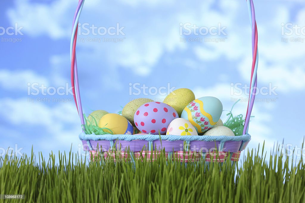 Easter basket in grass with blue sky stock photo