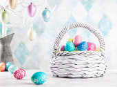Colourful Easter eggs sitting in a white basket.