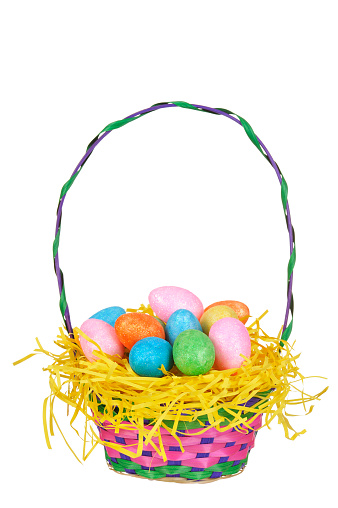 Multi colored eggs in basket isolated on white.