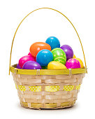 Multi colored Easter eggs in basket isolated on white background
