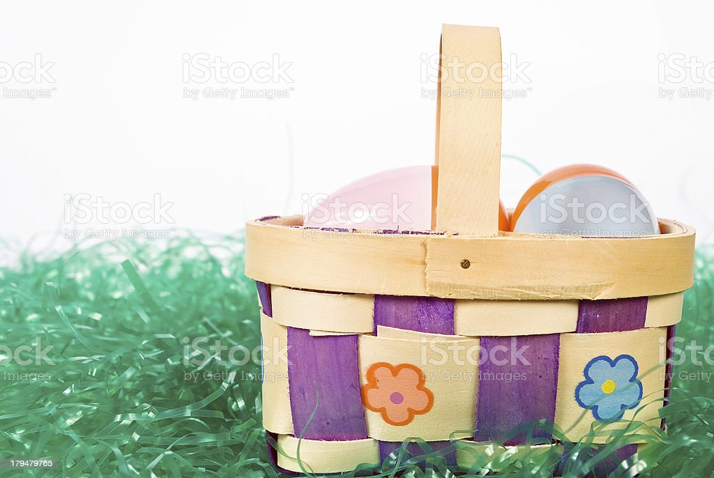 Easter basket wih colorful eggs sitting in artificial grass stock photo