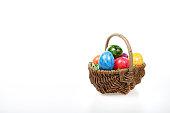 Osterkorb mit bunten Eiern auf weißem Hintergrund