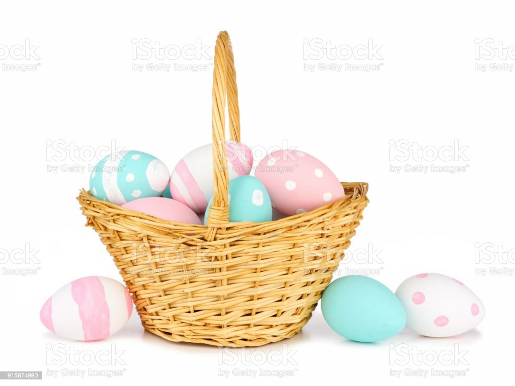 Easter basket with hand painted pastel Easter Eggs over white stock photo