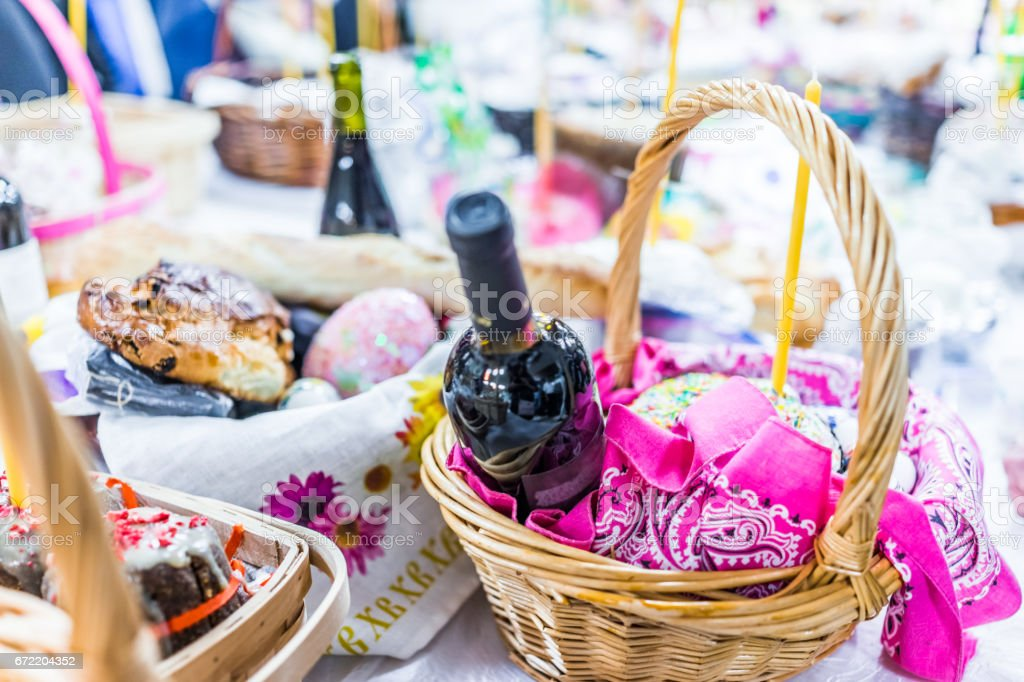 Easter basket with Kulich cake, wine and candles on table in church stock photo