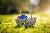 Easter basket with traditional painted eggs in the garden or grass.
