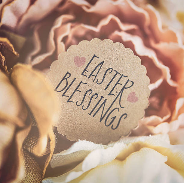 Easter Blessings message amidst fabric flowers stock photo