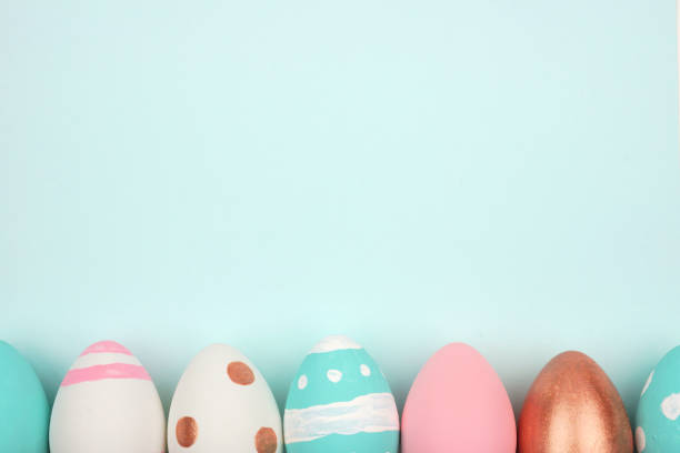 Easter bottom border of pink, white, blue and rose gold eggs against a pastel blue background stock photo