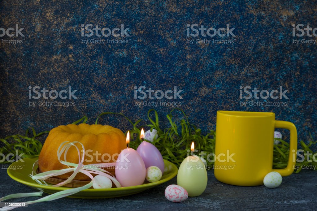 Easter bread on green plate, yellow mug and painted Easter eggs on...