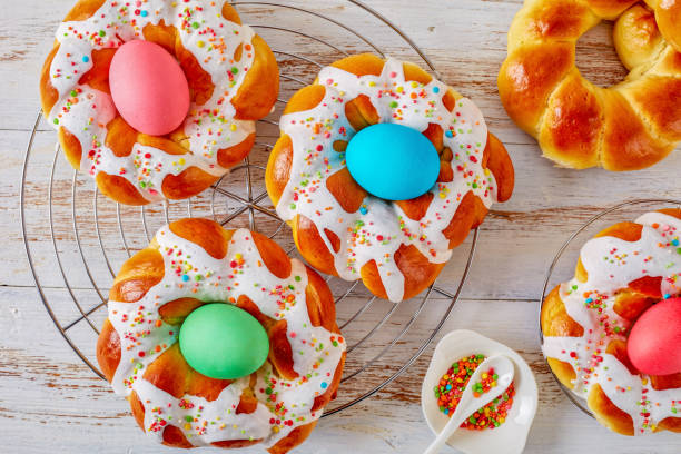 easter bread rings glazed around dyed egg - greek easter stock photos and pictures