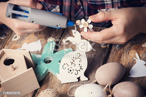 Female hands holding wooden easter bunny and hot glue gun, DIY composition on rustic wooden table