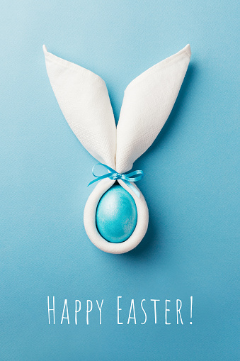 istock Easter bunny ears with egg on blue background. 1138812611