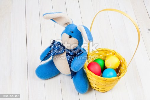 Easter bunny, eggs in basket on white wood background