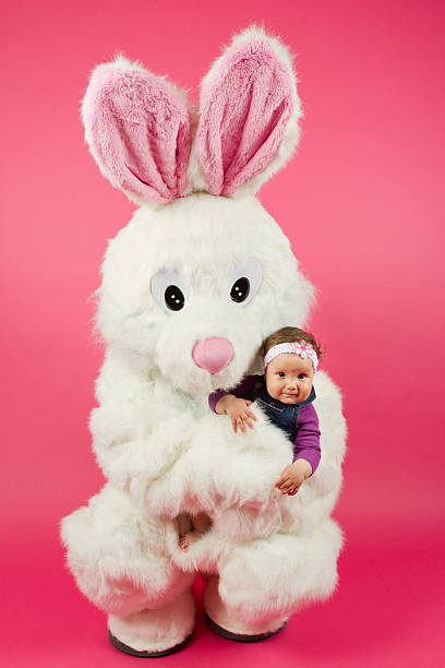 easter bunny hugging little baby girl - easter bunny stock photos and pictures