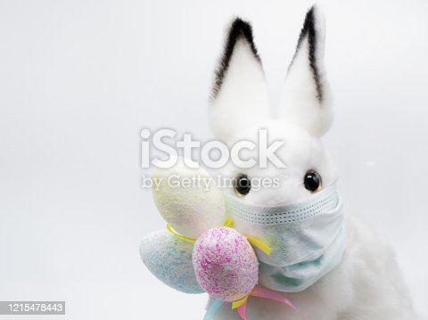 istock Easter Bunny in a facial medical mask with a bouquet of colorful eggs. The concept of Easter and quarantine during coronavirus. Like a postcard wishing you well 1215478443