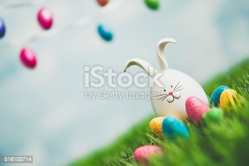 istock Easter bunny in grass with Easter egg garland 516103714