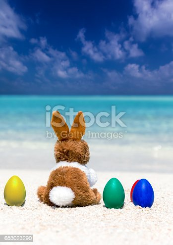 istock Easter bunny on colored easter eggs 653023290