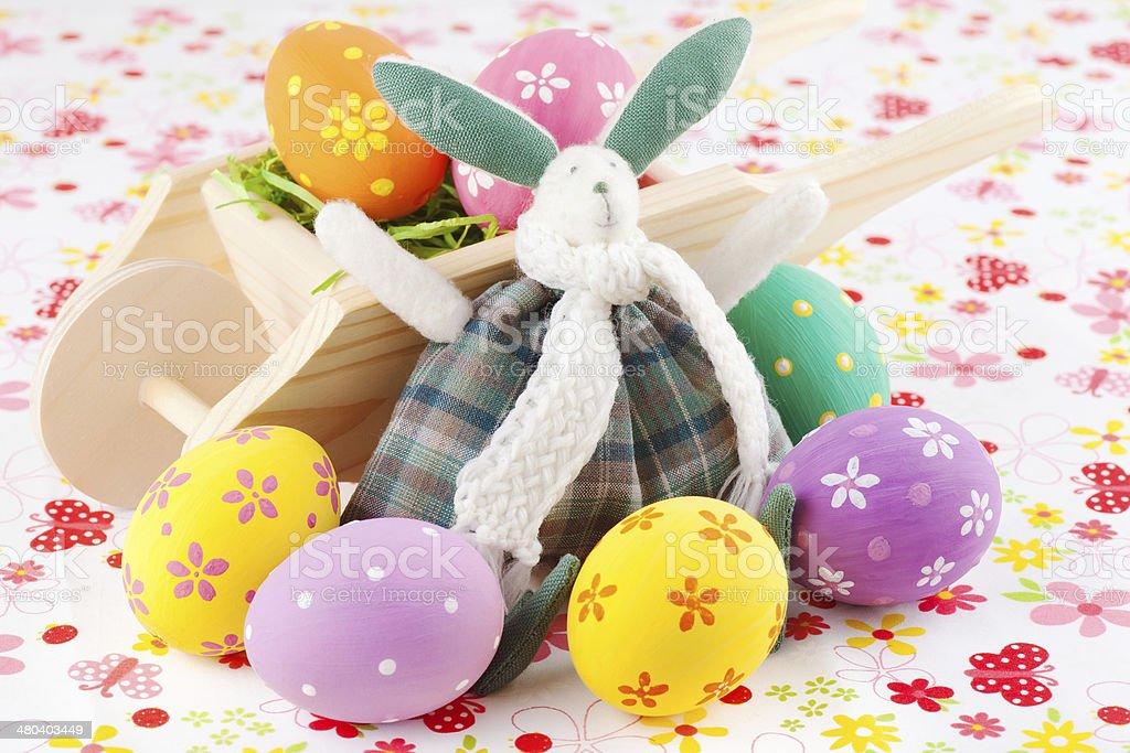 Easter bunny rabbit with a wheelbarrow and eggs stock photo