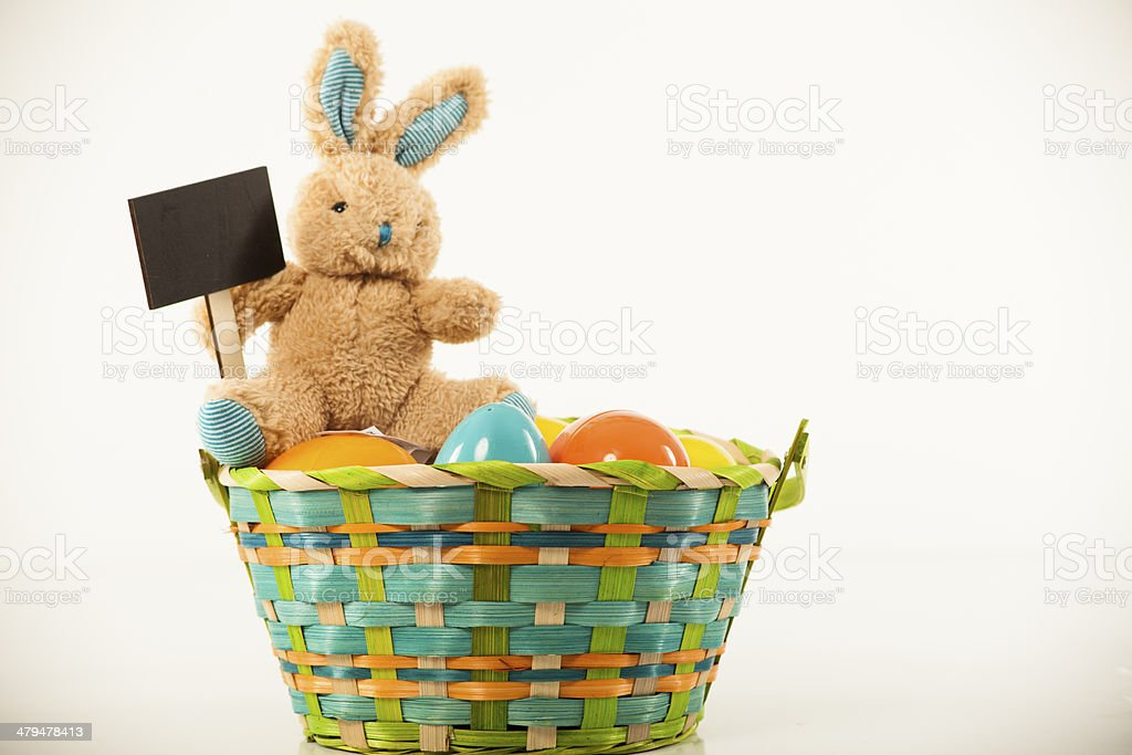 Easter Bunny sitting on a basket of eggs with sign stock photo
