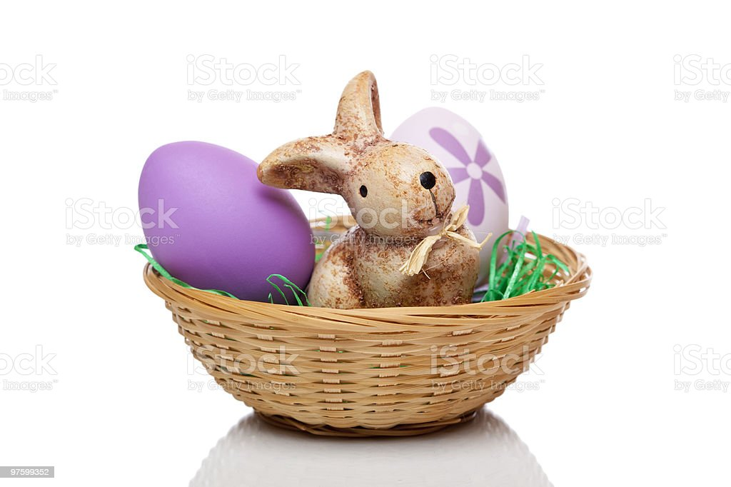 Easter bunny sitting with eggs in basket royalty-free stock photo
